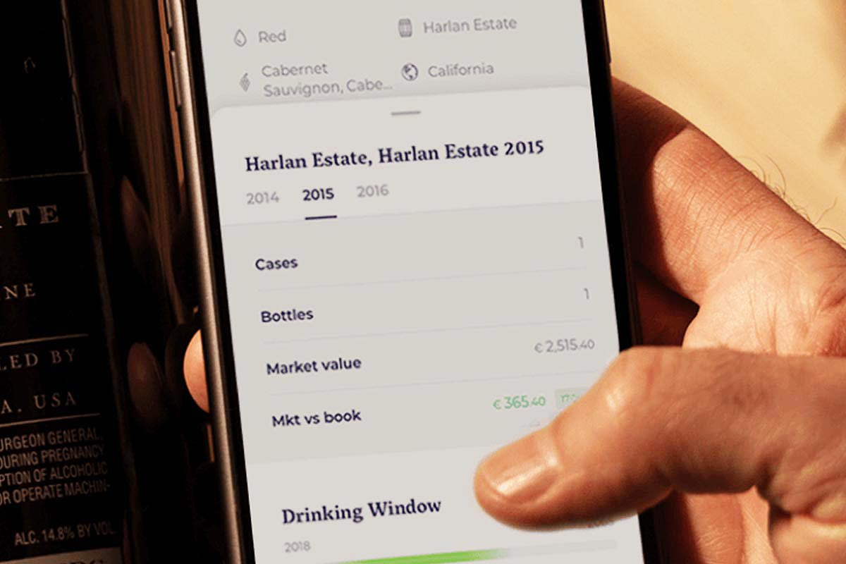 A hand holding a phone with the 1275 wine collector's app open
