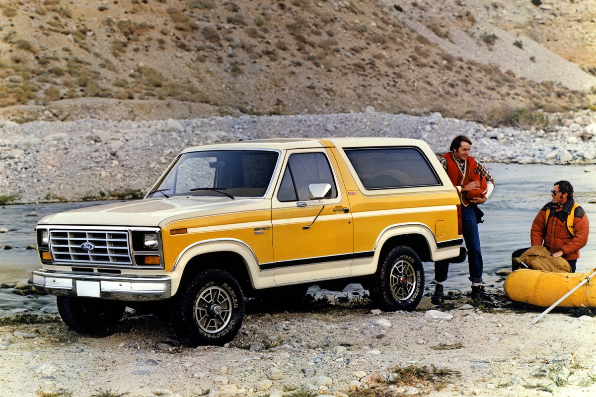 A white and yellow 1982 Ford Bronco SUV sitting among rocks and a river next to two outdoorsmen in a retro photo
