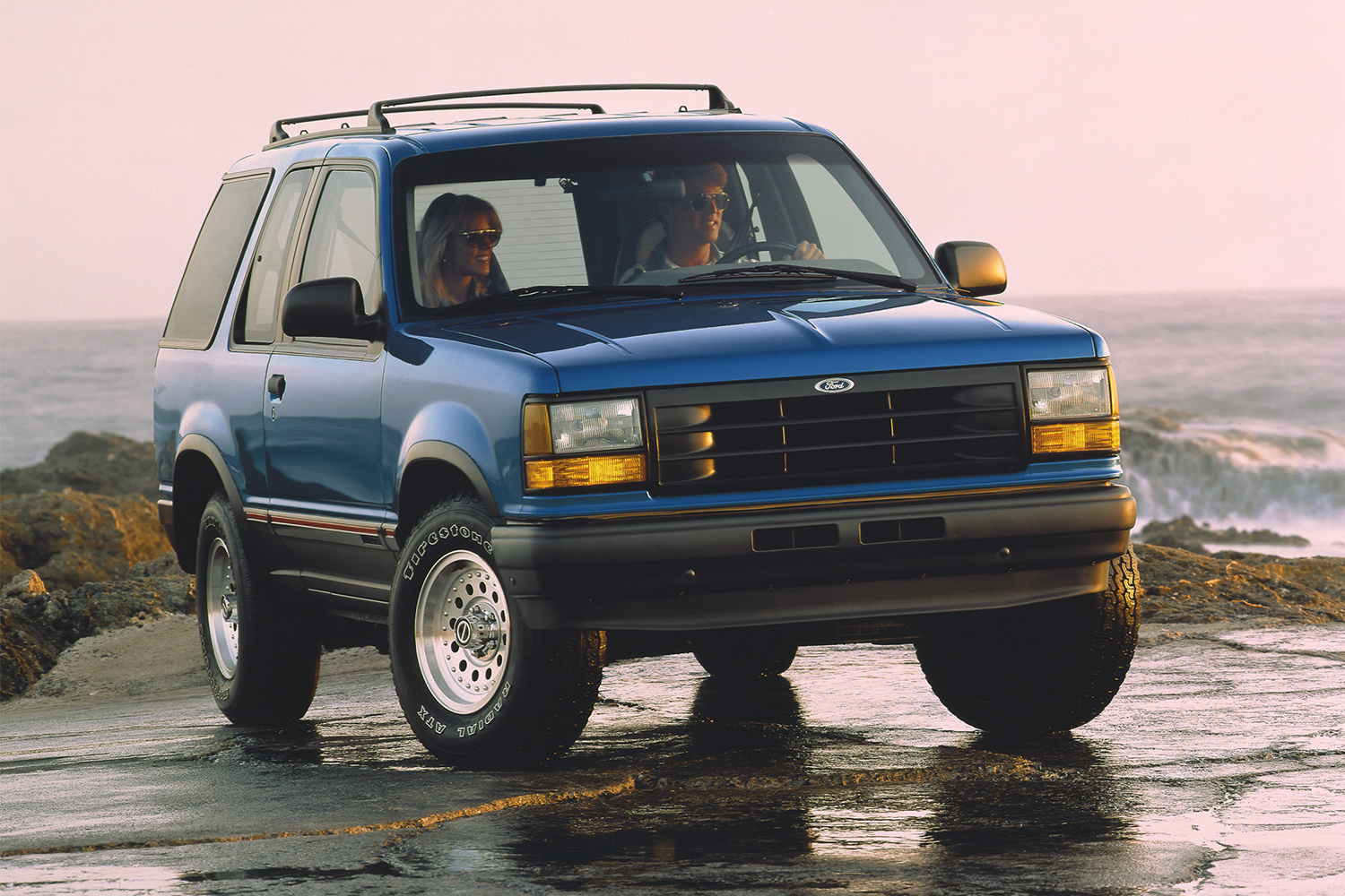 A man driving a 1992 blue Ford Explorer SUV near the ocean in a vintage photo