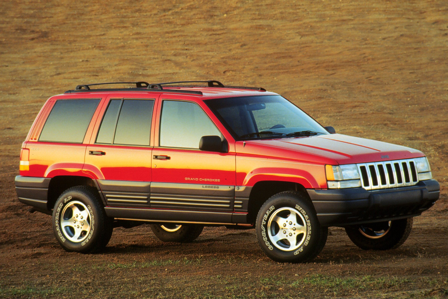 A 1996 Jeep Grand Cherokee Laredo in red sitting on the dirt in a vintage photo