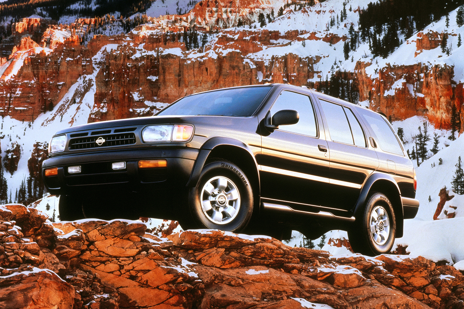 A 1997 Nissan Pathfinder SUV perched on a mountain with snow covered rock in the background in a vintage photo