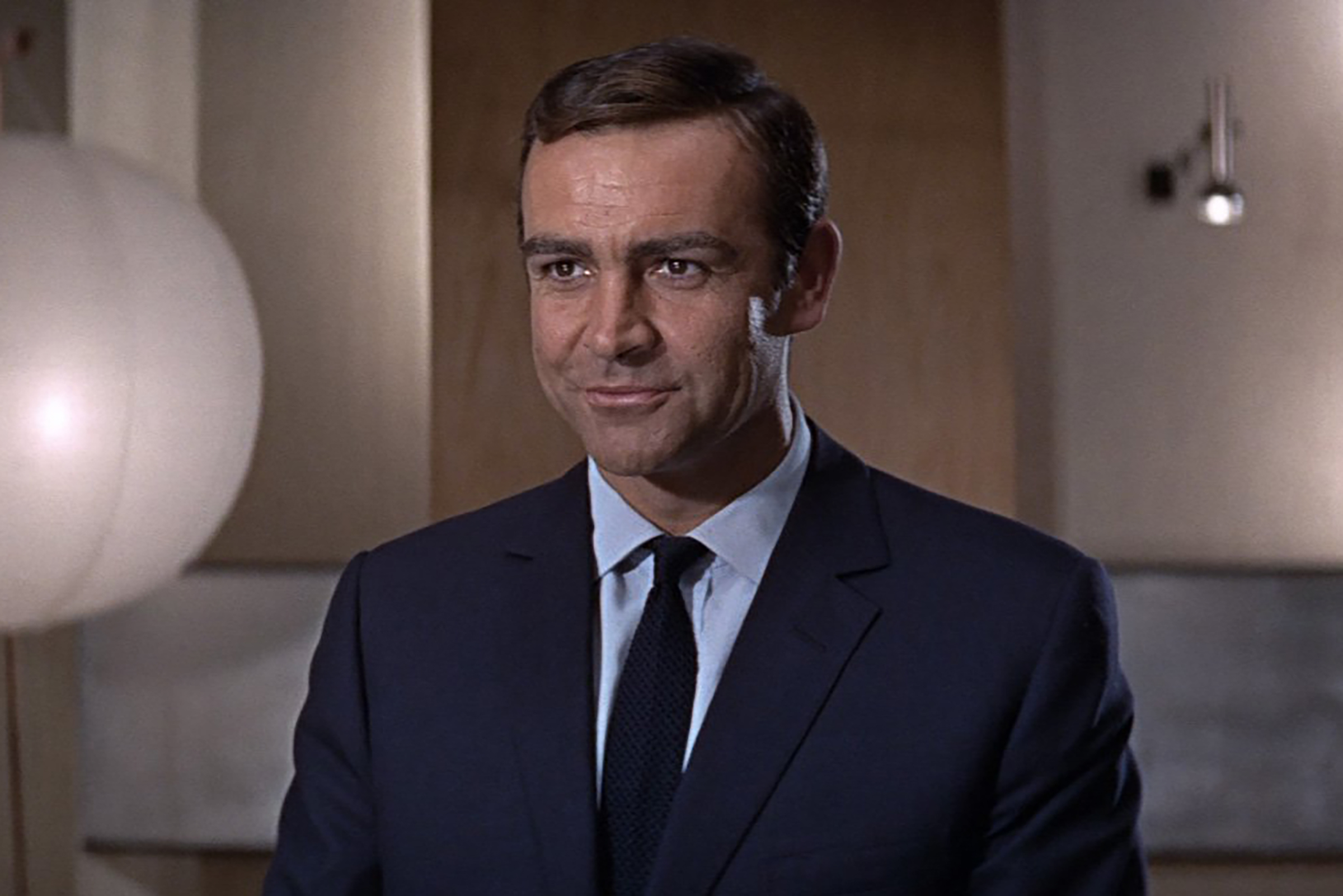 Connery wears a rich flat navy suit with a single button in You Only Live Twice.