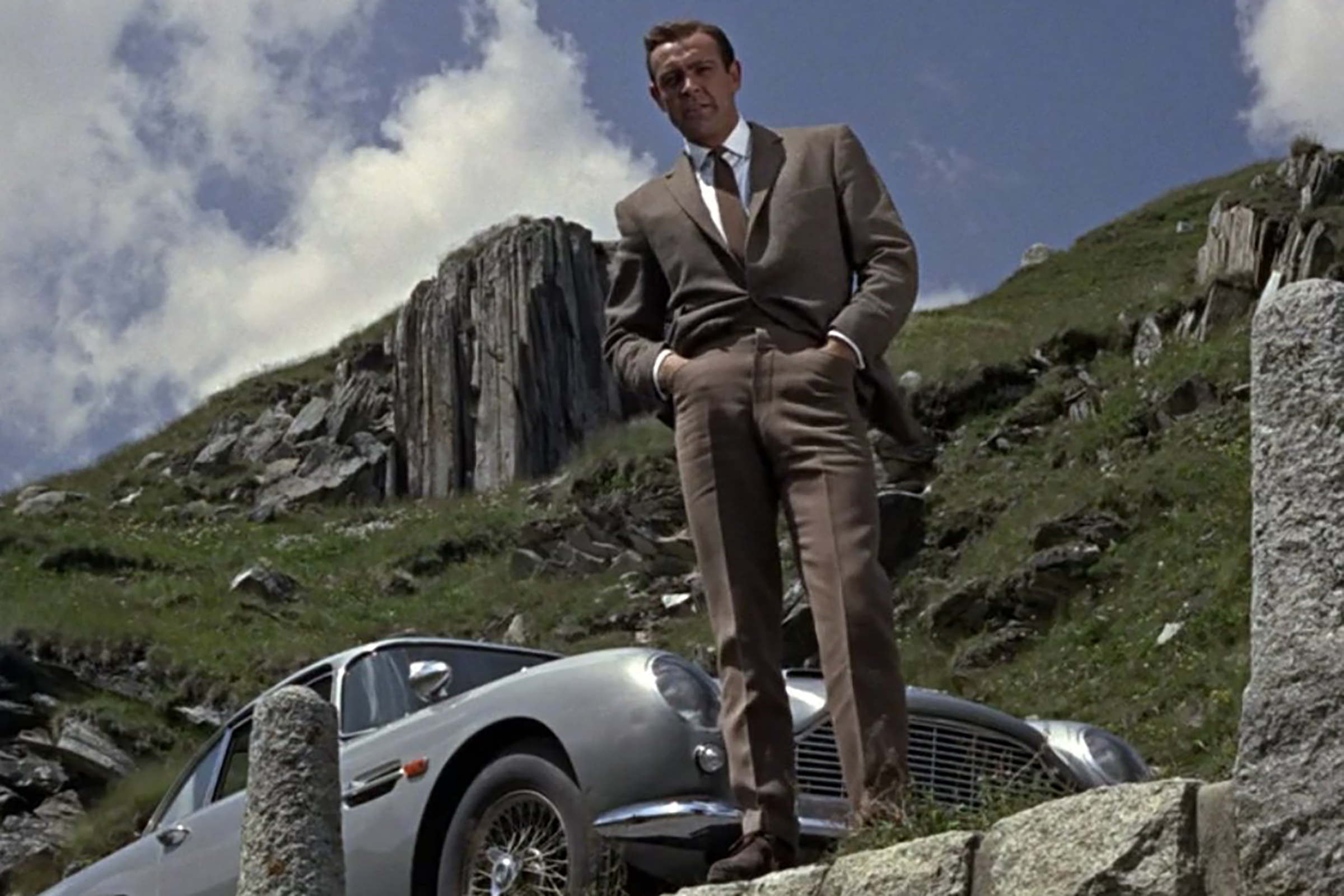 Connery wears a brown knit tie with a white shirt and tan trousers with a perfect half break in Goldfinger.