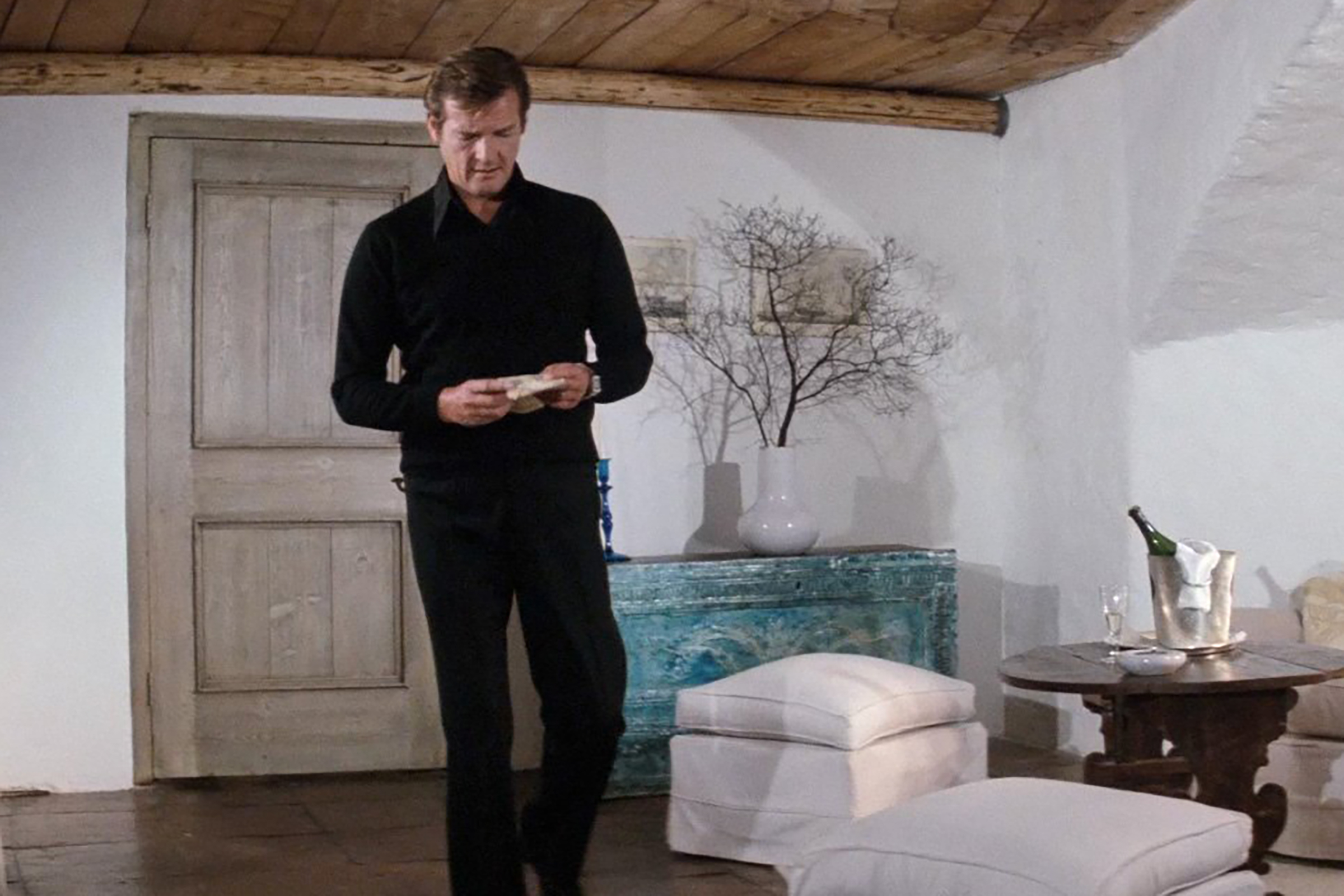 Moore sports black trousers and a black button down layered under a black v-neck sweater in The Spy Who Loved Me.
