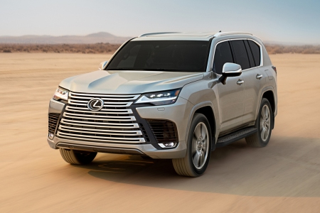 The 2022 Lexus LX 600 SUV with a large front grille driving through the desert on sand during the day