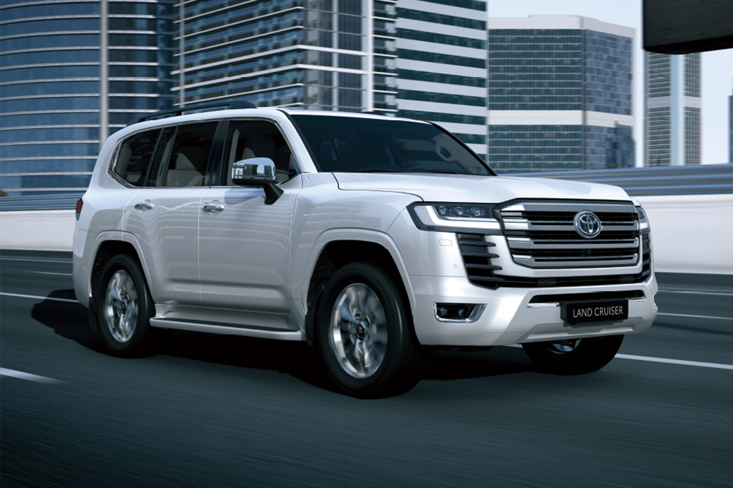 The 2022 Toyota Land Cruiser SUV in white driving down a road in the city