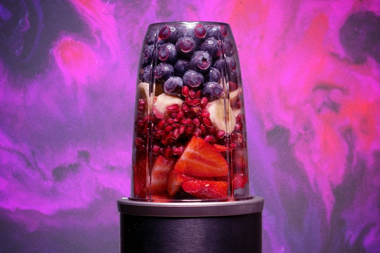 Fruit smoothie against a colorful purple background.