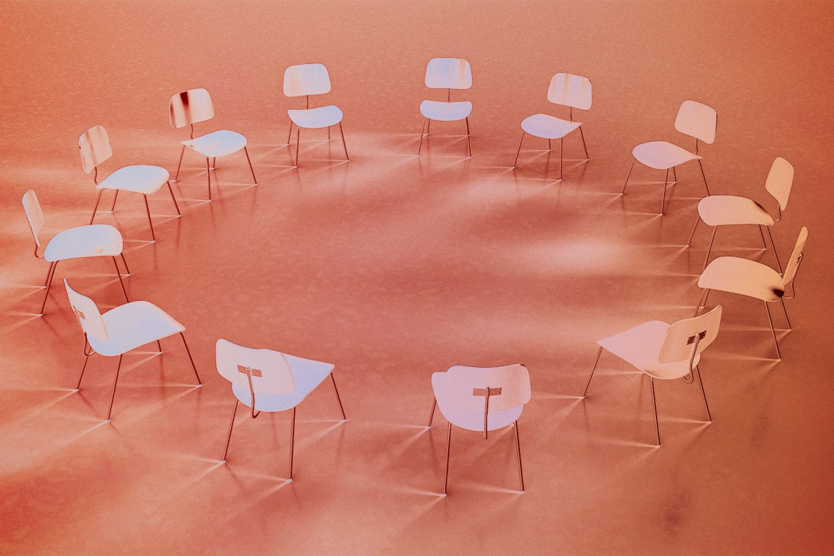 A circle of empty chairs against a light red background.