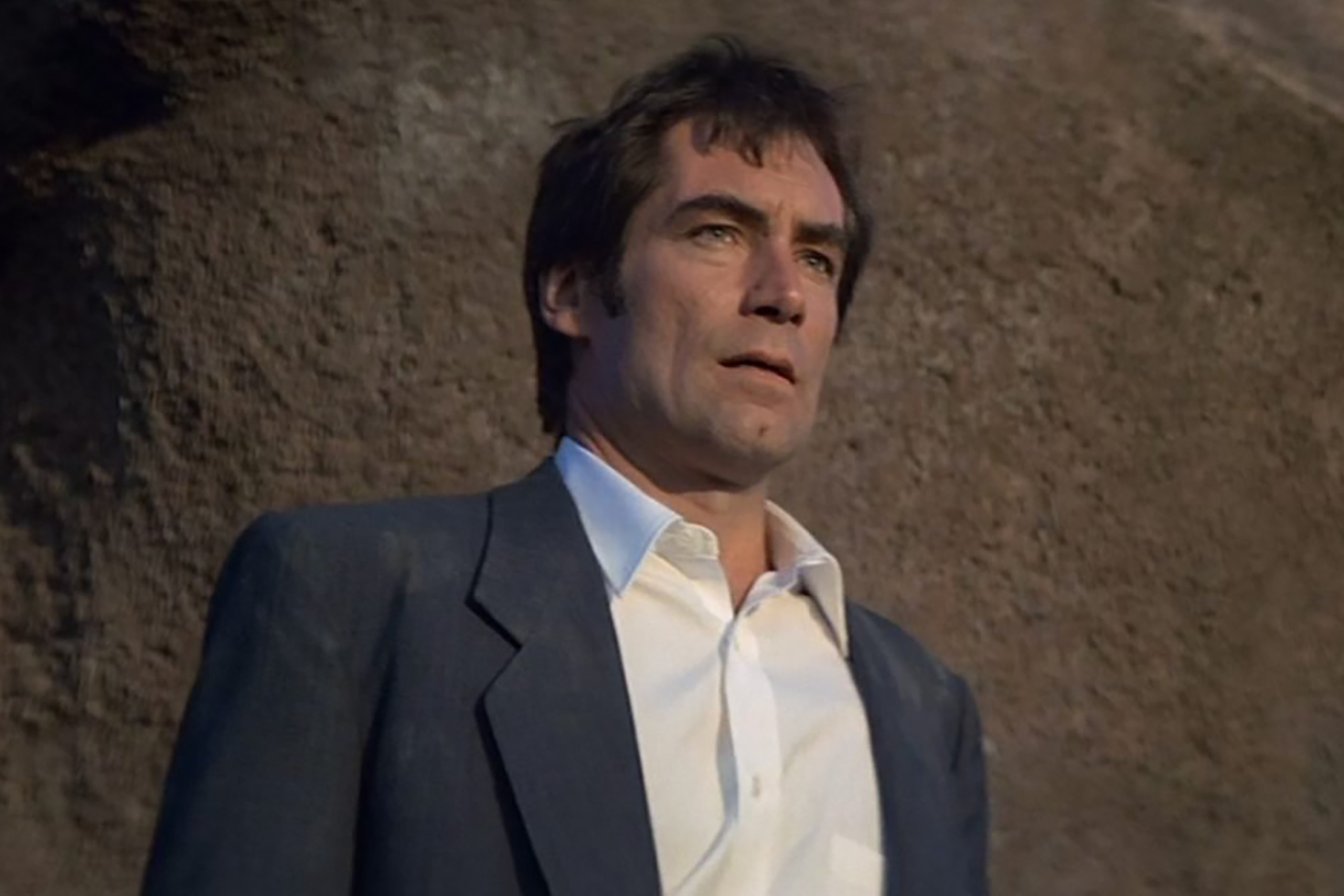 Timothy Dalton dons a simple navy suit and white shirt in License to Kill.