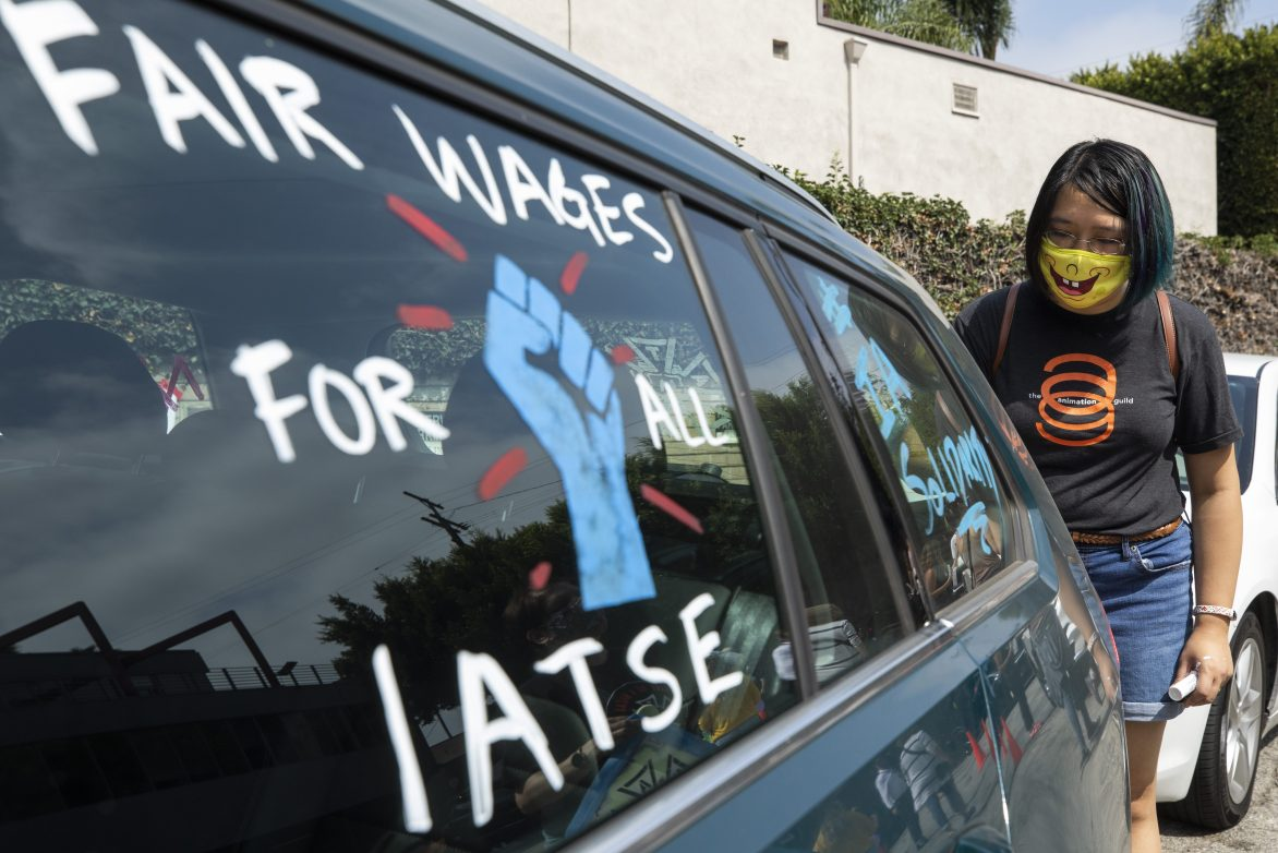 Crystal Kan, a storyboard artist, draws pro-labor signs on cars of union members during a rally at the Motion Picture Editors Guild IATSE Local 700 on Sunday, Sept. 26, 2021 in Los Angeles.