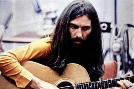 George Harrison playing acoustic guitar circa 1970.
