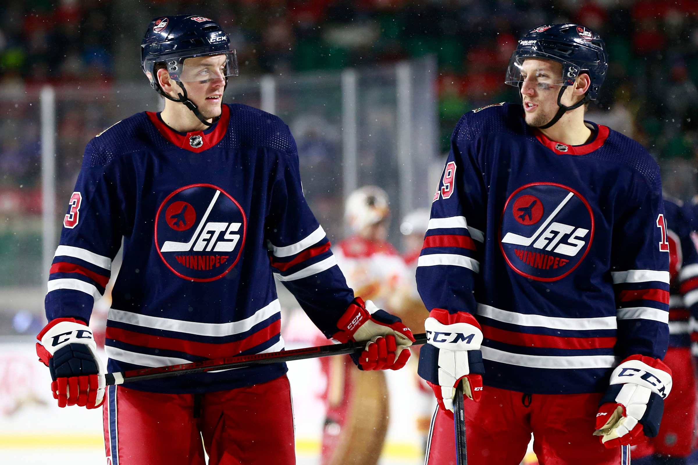Carl Dahlstrom #23 (L) and David Gustafsson #19 of the Winnipeg Jets stand talk while playing in the 2019 Tim Hortons NHL Heritage Classic against the Calgary Flames at Mosaic Stadium on October 26, 2019 in Regina, Canada