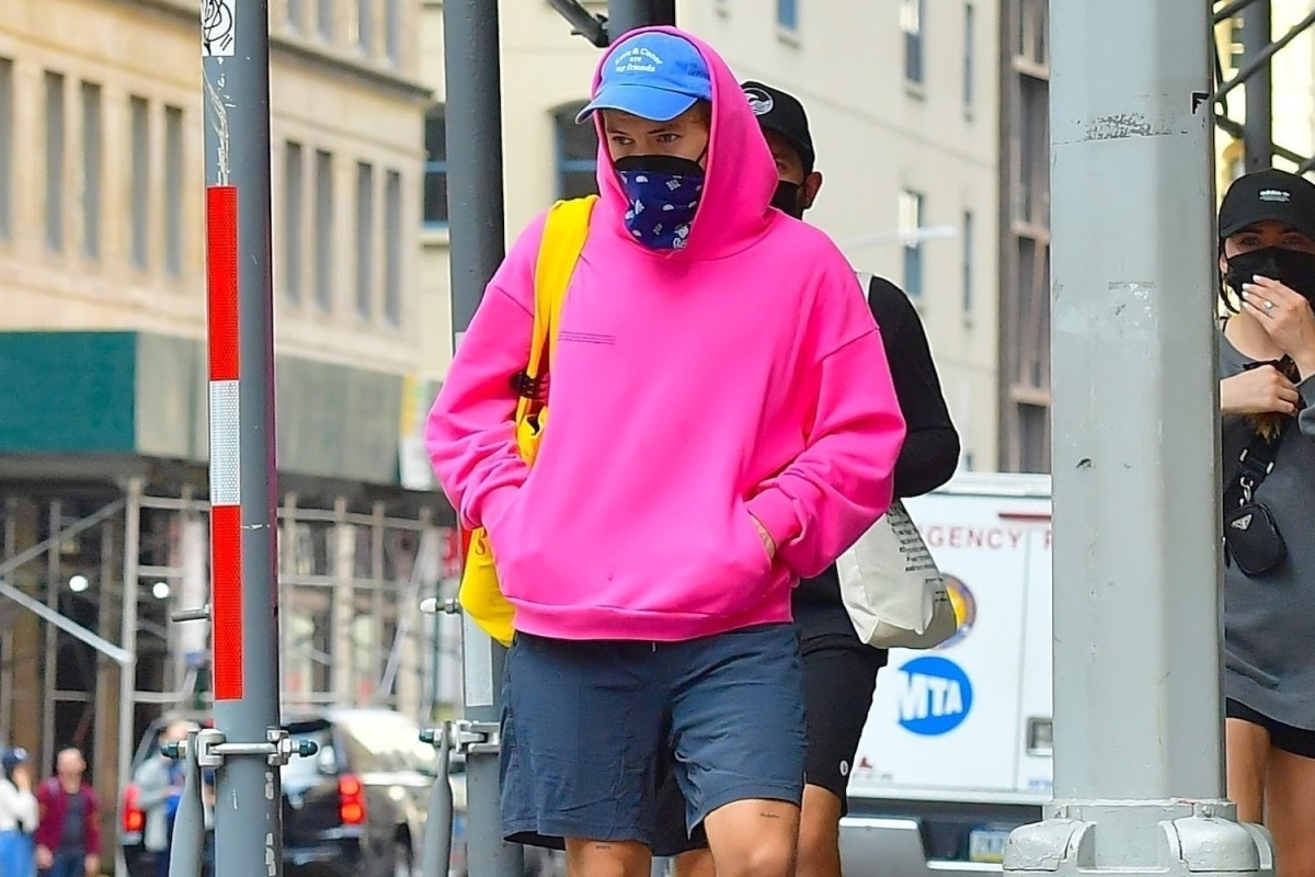 Harry Styles in a pink hoodie and navy shorts
