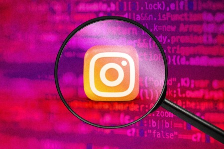 A magnifying glass looking at the Instagram icon on a pink and red background with computer code.