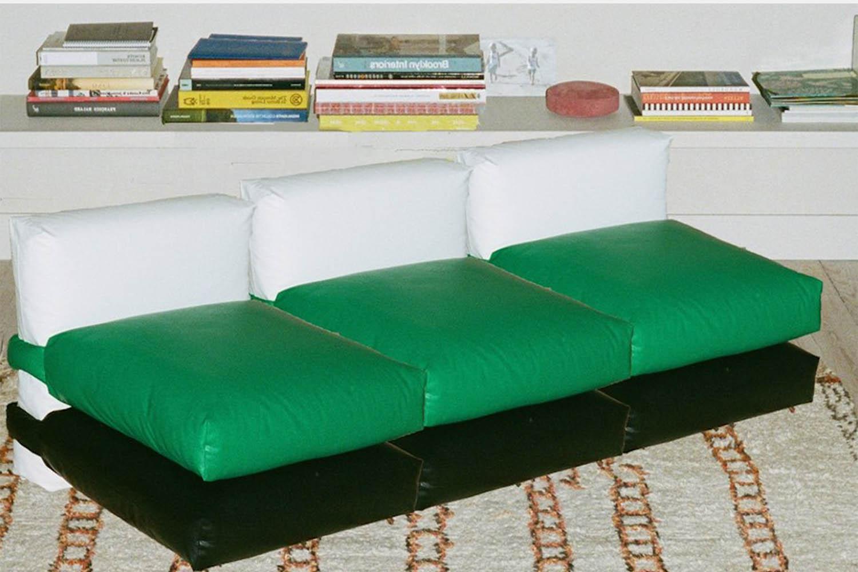 a green sofa made of pillows.