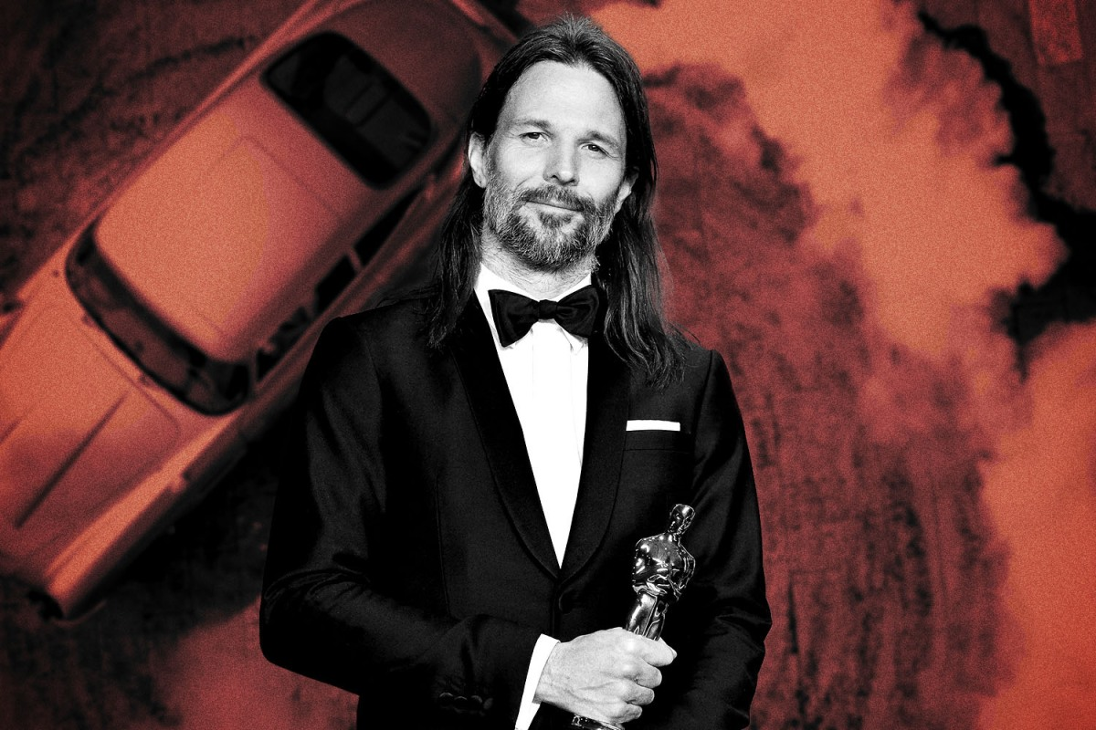 No Time to Die cinematographer Linus Sandgren holding the Oscar he won for La La Land, with James Bond's Aston Martin DB5 driving in the background
