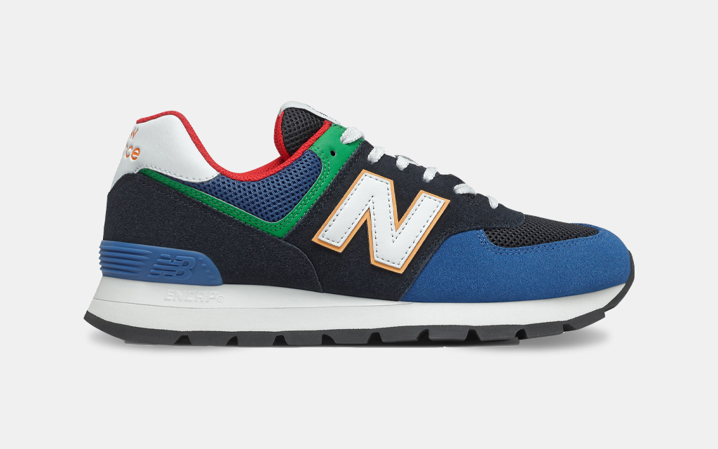 A side shot of the New Balance 574 Rugged Shoe in a black and captain blue colorway. The sneakers are on sale at REI in October 2021.