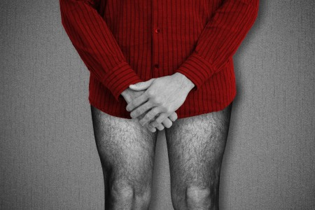 Black and white photo of a man wearing a red shirt and no pants with his hands clasped over his crotch