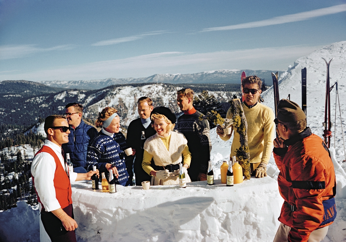 Skiers celebrating with a little après-ski atop a snowy mountain, captured by photographer Slim Aarons.