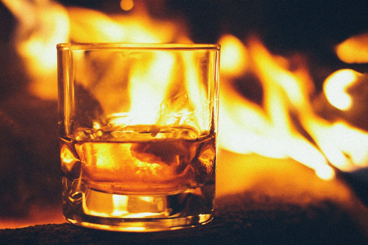 Smoky American whiskeys are a trend; pictured here, a glass of whiskey by a campfre