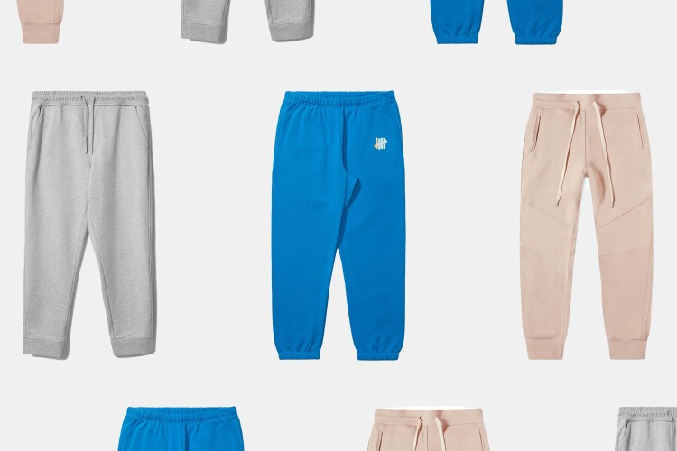 Grey sweatpants from Everlane, blue sweatpants from Undefeated and pink sweats from John Elliott, arranged in three rows on a grey background