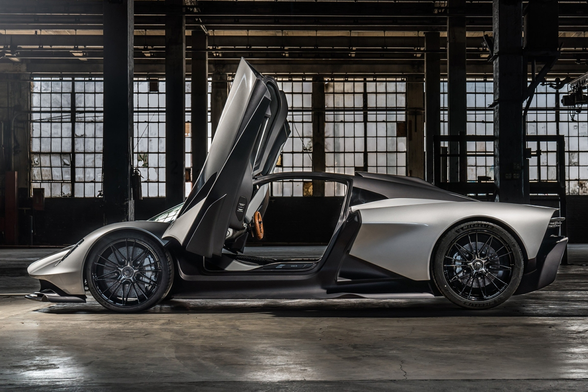 A side profile of the original Aston Martin Valhalla hypercar with the wing doors open so you can see through the car to the warehouse windows behind it