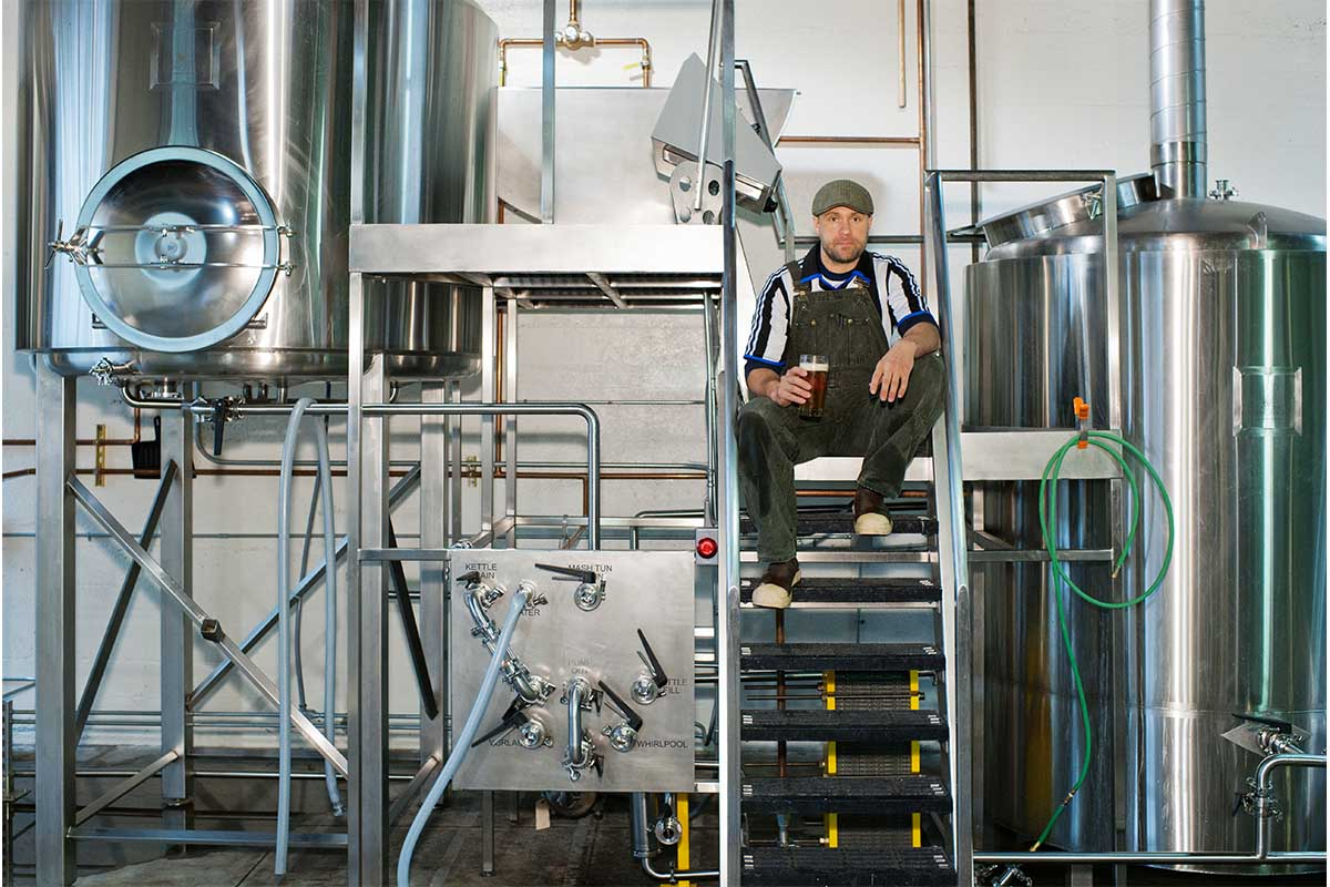 Man sitting in a brewery drinking a beer on some steps. A new survey by the Brewers Association suggests most U.S. brewery owners are white and male.