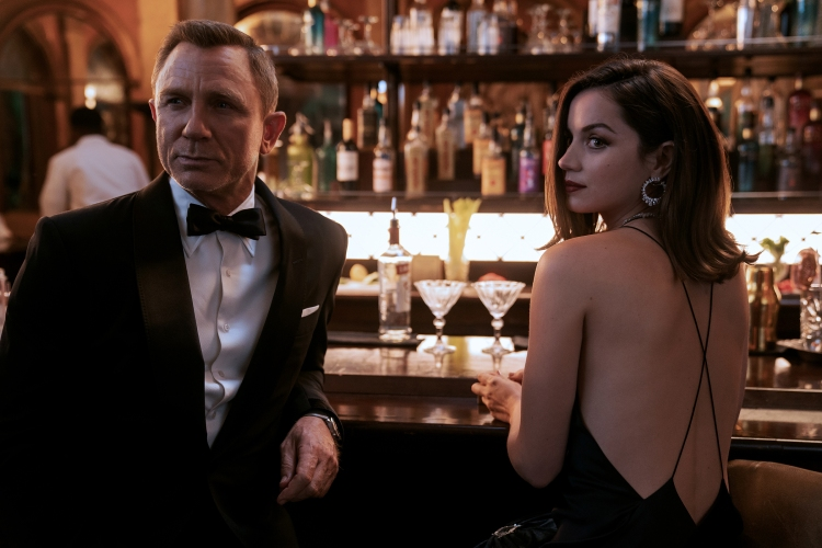 James Bond (Daniel Craig) and Paloma (Ana de Armas) sit at a bar in NO TIME TO DIE, an EON Productions and Metro-Goldwyn-Mayer Studios film