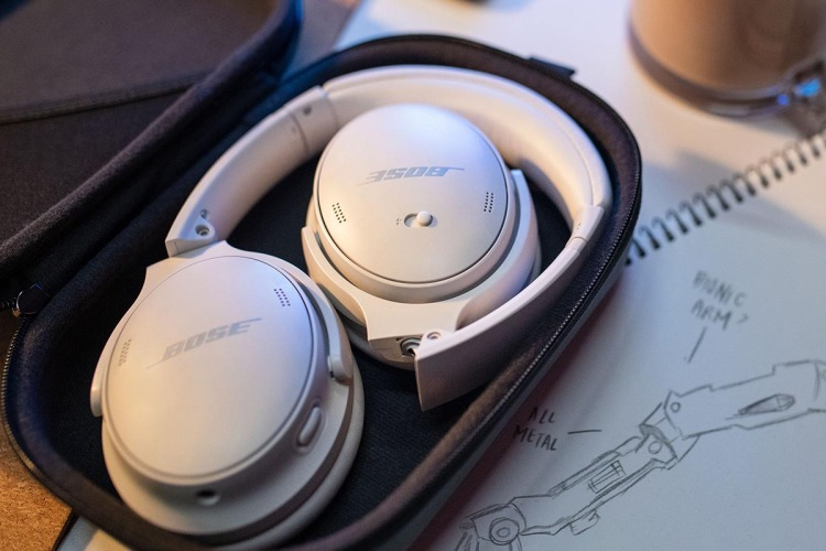 A pair of smoke white Bose QuietComfort 45 headphones lying in their case on a desk. The new headphones offer excellent noise cancellation.