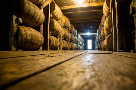 Bourbon barrels aging in a warehouse. Kentucky distilleries are getting hit hard by state taxes and international tariffs.