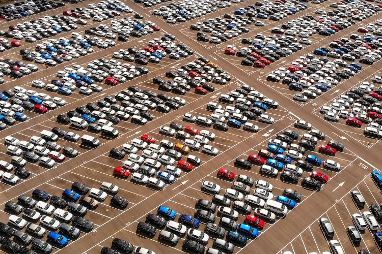 Hundreds of parked cars, trucks and SUVs in a large parking lot during the day