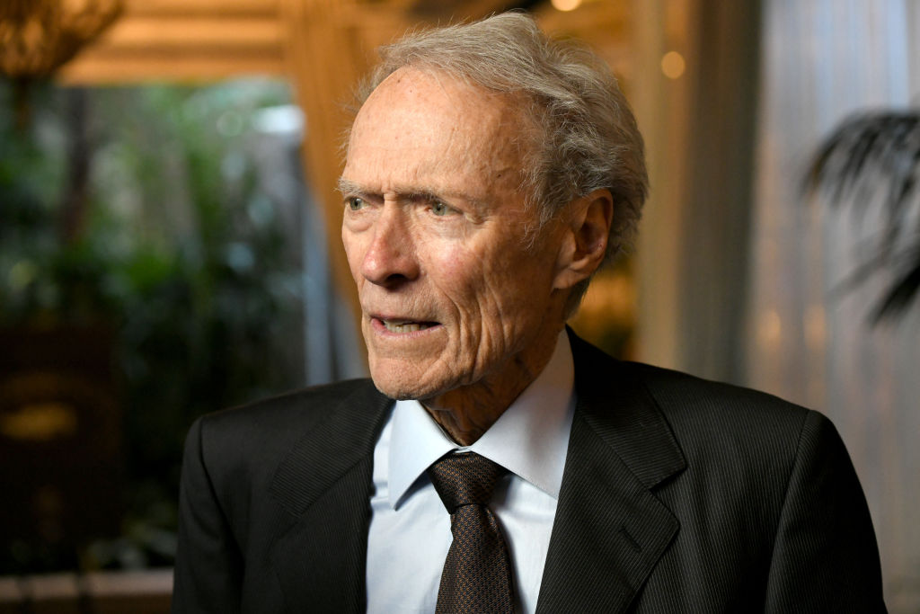Director Clint Eastwood in a suit and tie looking off to his right