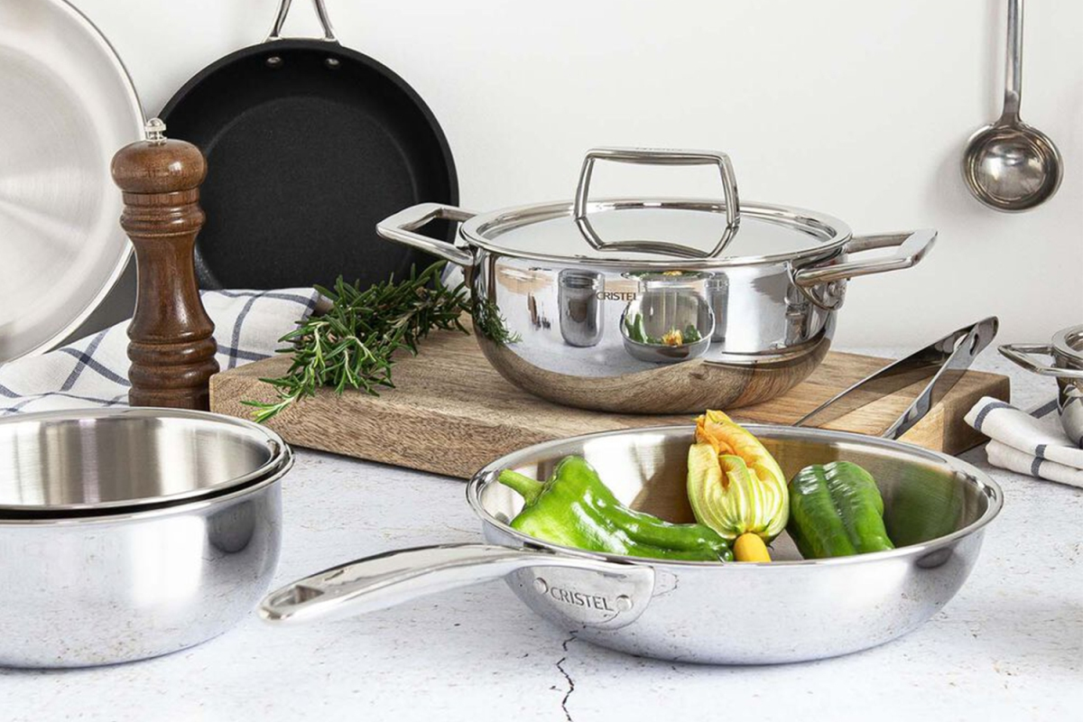 French Cristel stainless steel skillets and nonstick pans on a table with a cutting board and some assorted vegetables