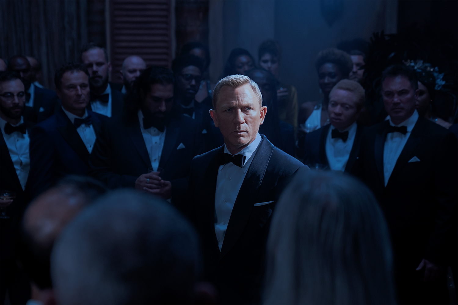 """Daniel Craig as James Bond pictured in a tuxedo in """"No Time to Die,"""" surrounded by enemies from the secret organization Spectre"""