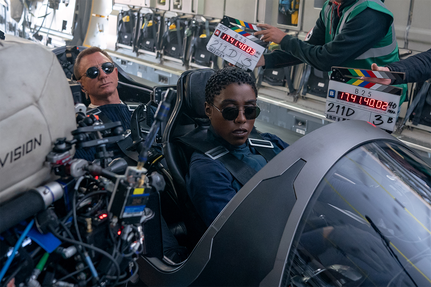 """Daniel Craig (who plays James Bond) and co-star Lashana Lynch (who plays Nomi) with cameras pointed at them during the filming of a scene in """"No Time to Die"""""""