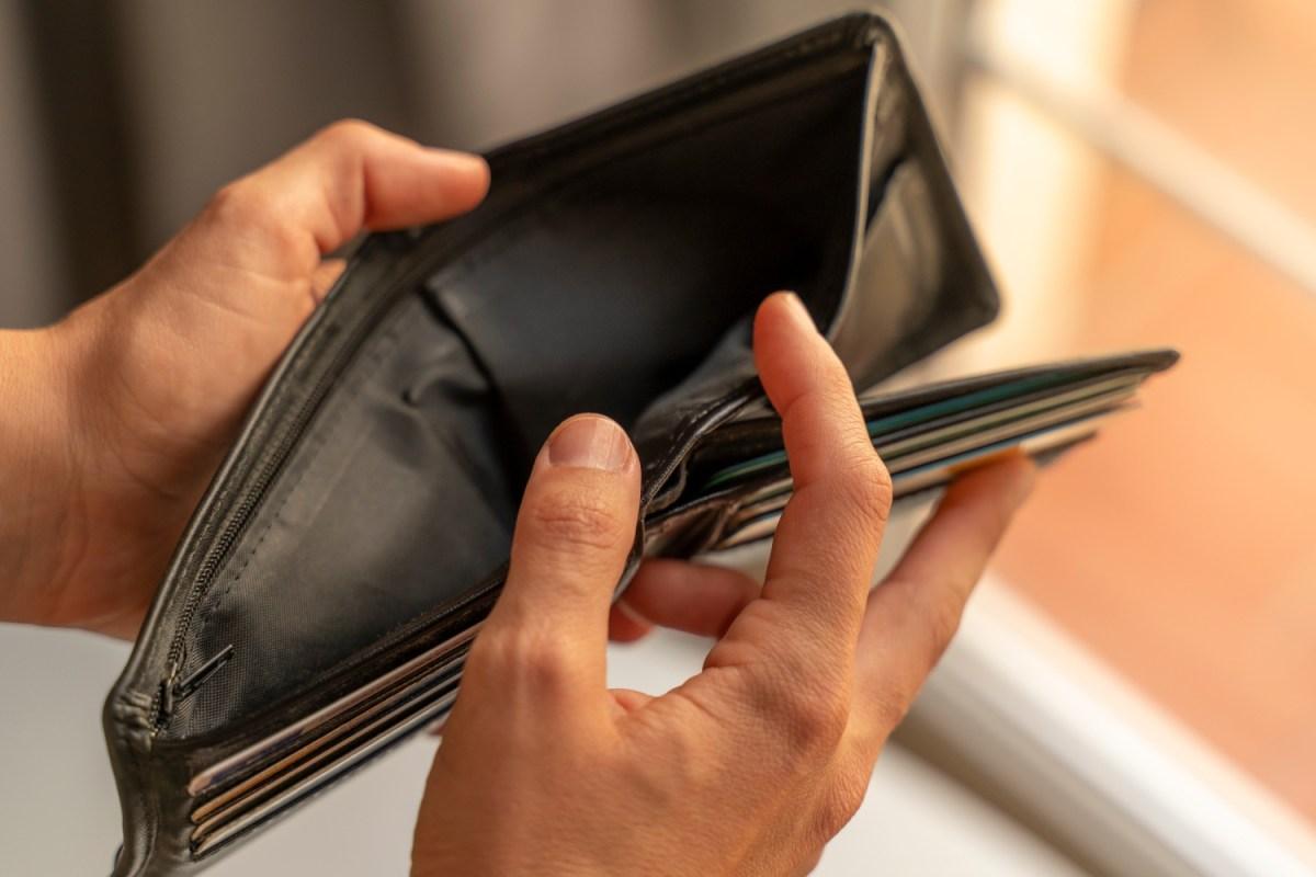 Man's hands opening up empty wallet