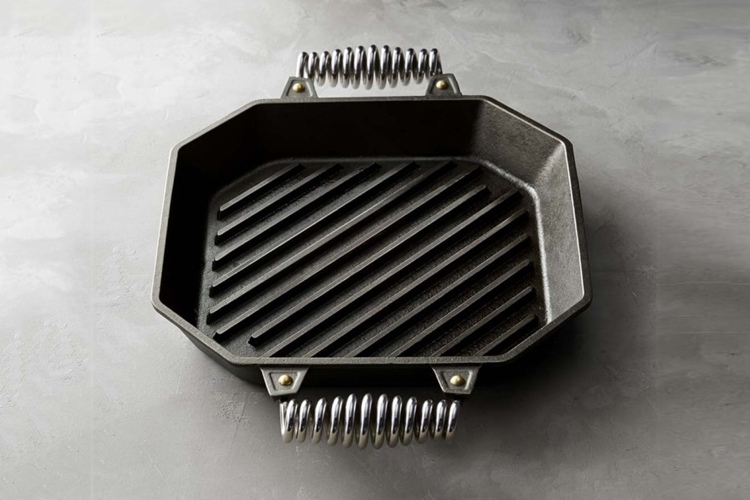 A 12-inch cast iron grill pan from Finex with coiled stainless steel handles on a grey table. It's currently on sale at Williams Sonoma.