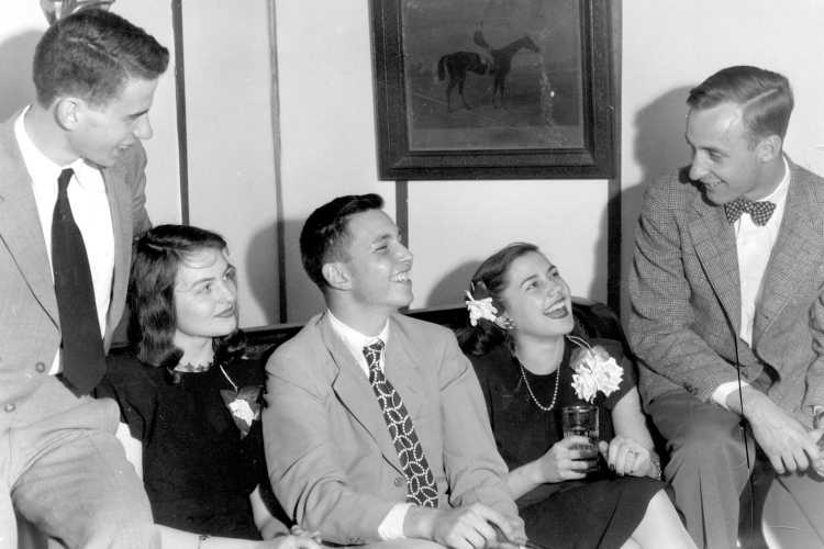 At a party hosted by the Delta Phi fraternity at Johns Hopkins University, brothers lounge on a sofa in a group, wearing suits next to their girlfriends in dresses and corsages, everyone smiling and drinking beverages from glasses, in a fraternity house right off campus, Baltimore, Maryland, 1947.