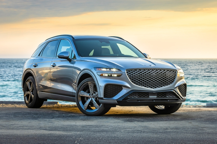 The Genesis GV70 SUV with the headlights on sitting still with a beach and sunset in the background