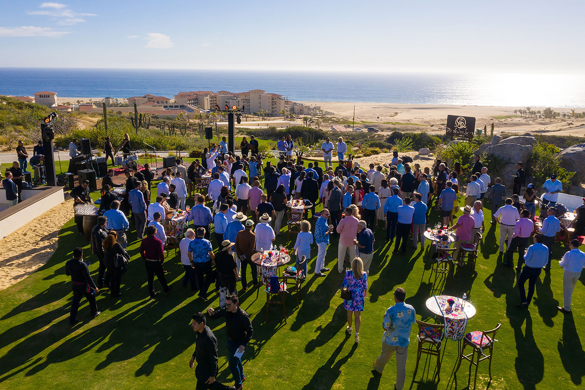 People gather at the opening of the Rancho San Lucas golf course overlooking the ocean.