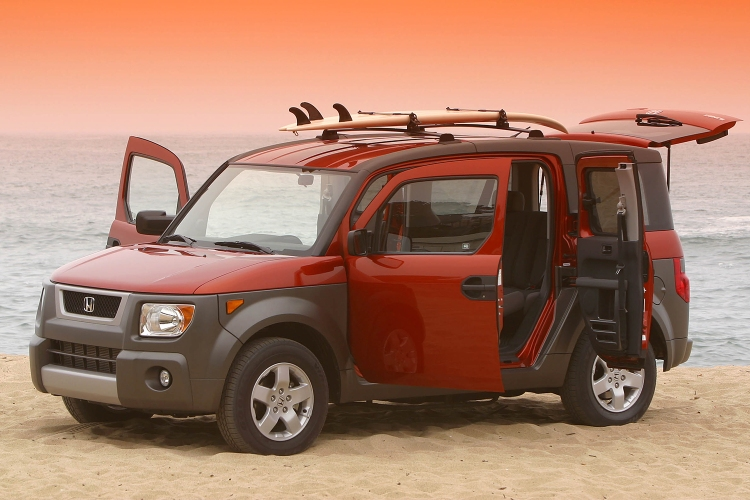 An orange and brown Honda Element with all the doors open and a surfboard on top sitting on the beach at sunset