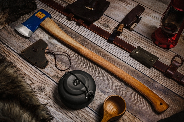 The Agdor 32 Yankee Felling Axe from Hults Bruk, available in the U.S. as of July 2021, lying on a wood table next to a leather sheath and other tools