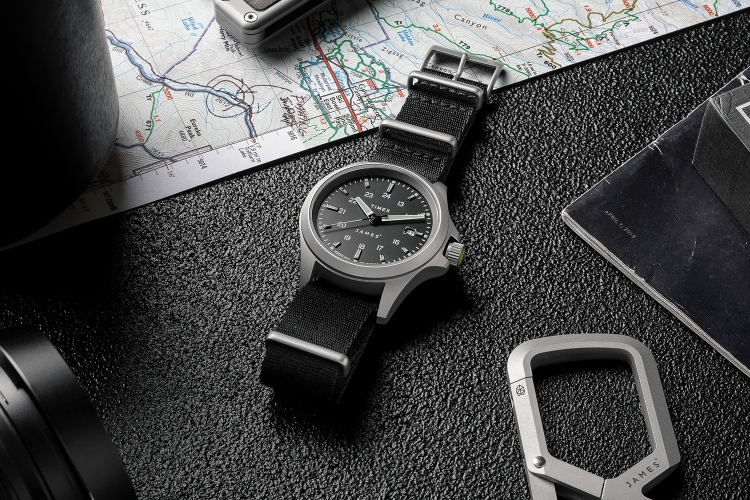 The new automatic watch from The James Brand and Timex lying on a table next to a map, pocketknife, keychain and coffee cup