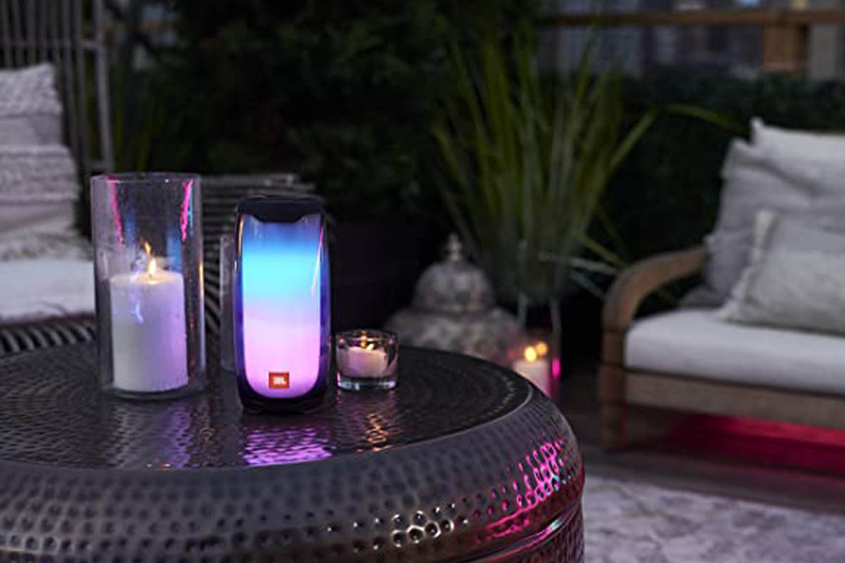A lit-up JBL Pulse 4 speaker on an outdoor table at night. The speaker is currently on sale at Woot.
