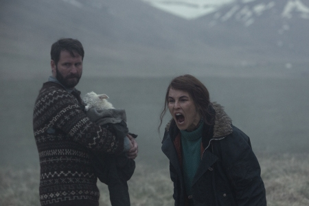 """In a still from the Icelandic horror movie """"Lamb,"""" a mother screams while a father holds their hybrid lamb-human baby"""
