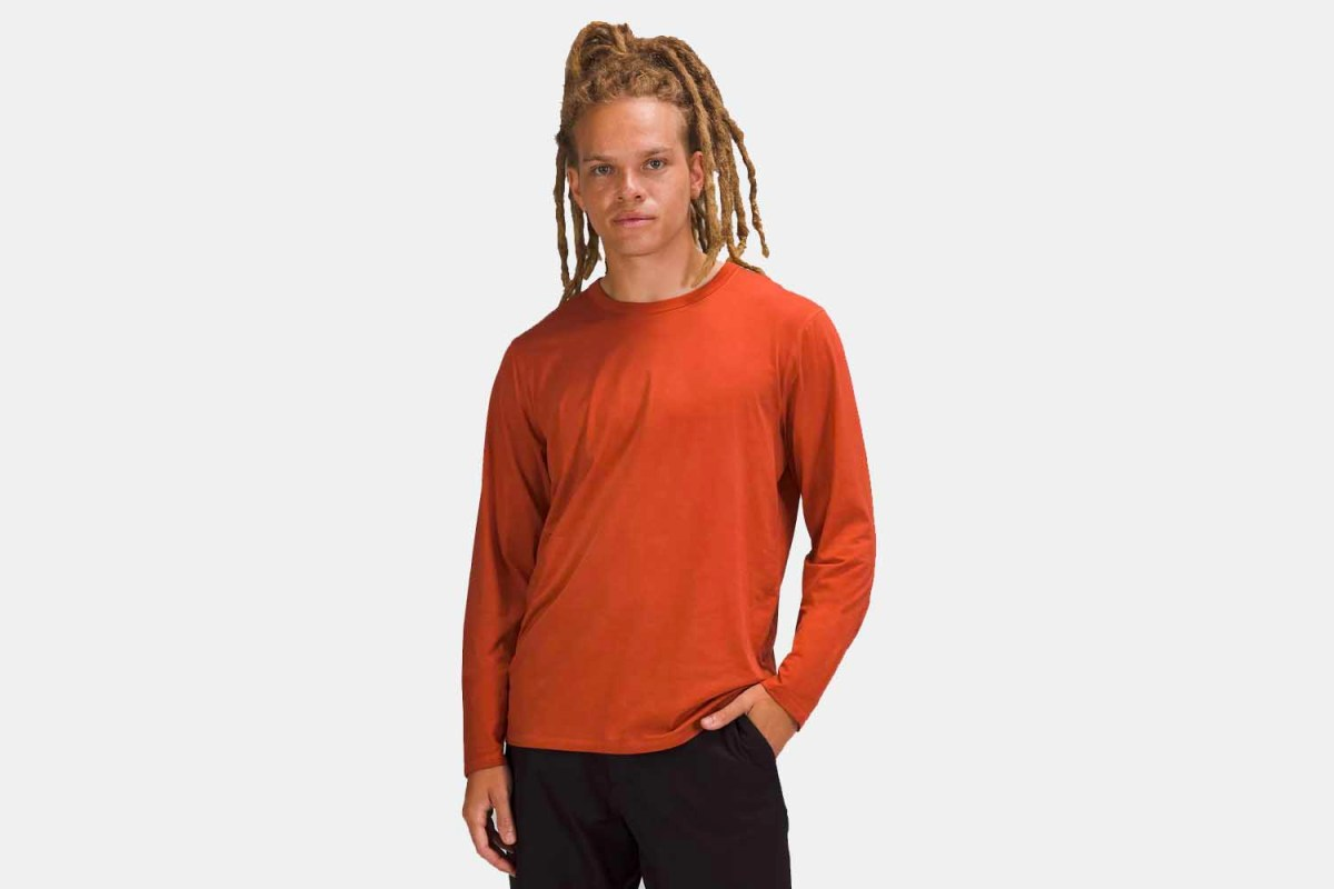 A man wearing Lululemon's Fundamental Long Sleeve workout shirt in orange