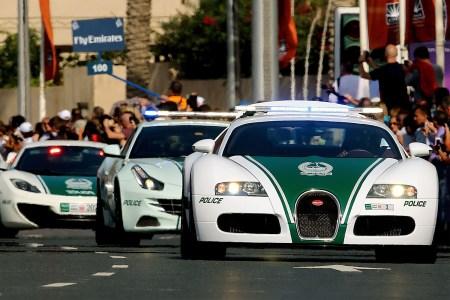 A United Arab Emirates police convoy driving down the street in Dubai featuring a Bugatti, Ferrari and McLaren police car