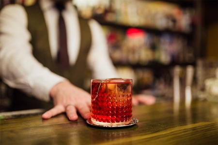A bartender serving a single Negroni at a bar. Some bars specialize or focus on just one cocktail.
