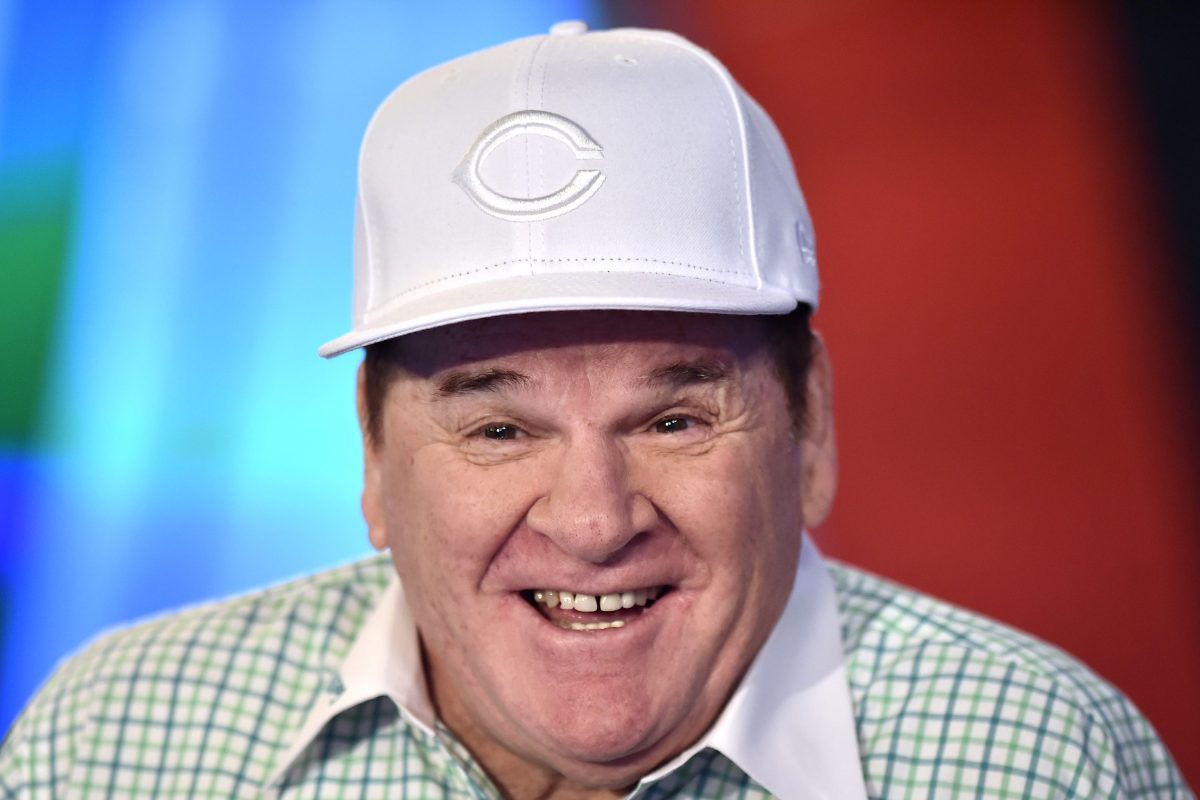 Pete Rose visits the Fox Business Network Studios wearing a white Cincinnati Reds hat and a green checker shirt with a white collar