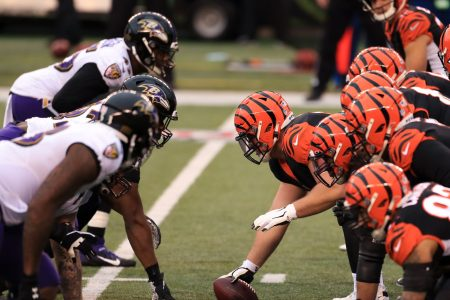 Baltimore Ravens and Cincinnati Bengals players line up for a play